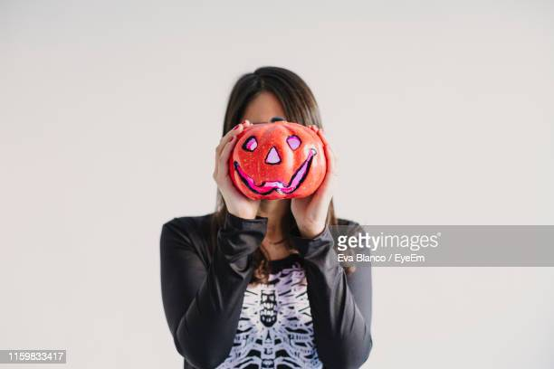 mid adult woman holding jack o lantern against white background - scary pumpkin faces stock photos and pictures