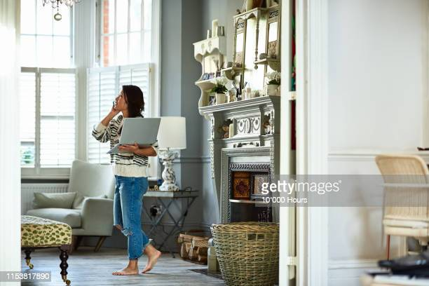 mid adult woman holding laptop and talking on phone - home interior stock pictures, royalty-free photos & images