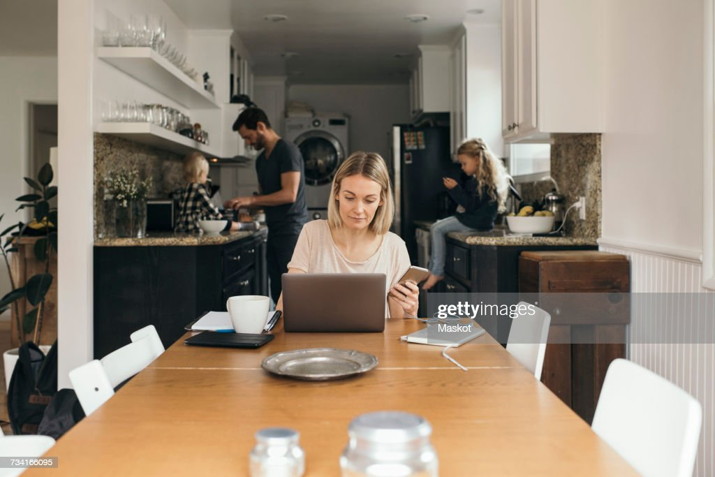 Mid adult woman holding mobile phone while using laptop at table with family in kitchen at home : Stock Photo