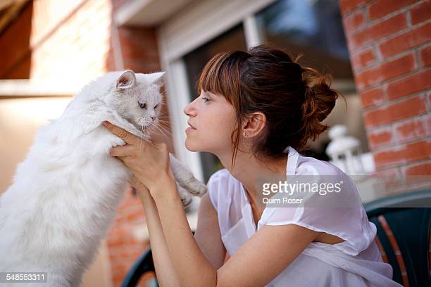 Mid adult woman holding reluctant cat on doorstep