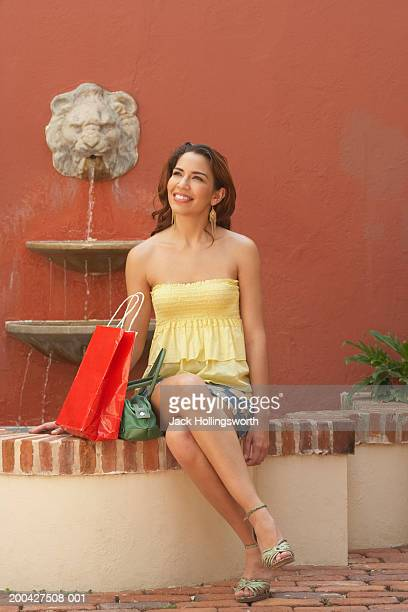 Mid adult woman holding shopping bags and smiling