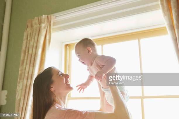 mid adult woman holding up baby daughter in bedroom - diaper girl photos et images de collection