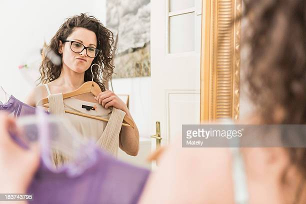 mid adult woman holding up dress in front of mirror - kleid stock-fotos und bilder