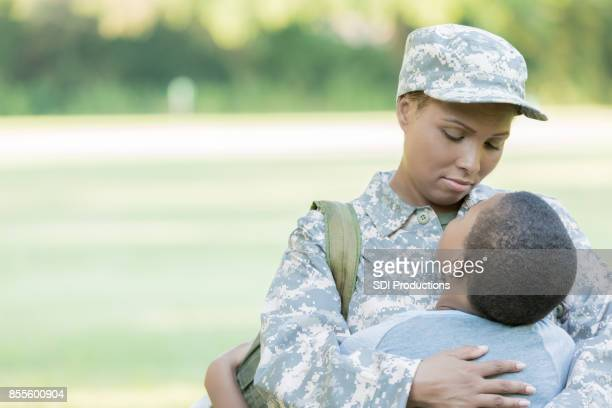 Mid adult woman hugs son before her deployment