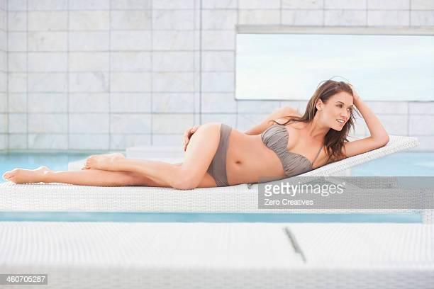 mid adult woman in bikini lying on pool sunbed - einzelne frau über 30 stock-fotos und bilder