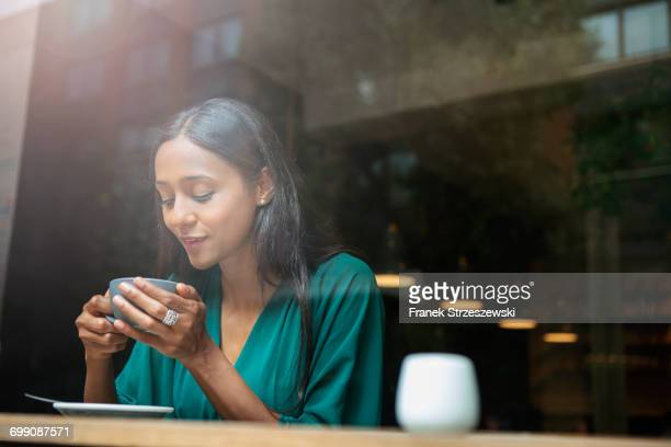 mid adult woman in cafe window seat looking down at coffee cup - down blouse stock pictures, royalty-free photos & images