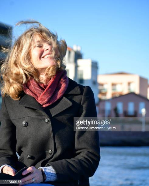 mid adult woman in city against sky - overcoat stock pictures, royalty-free photos & images