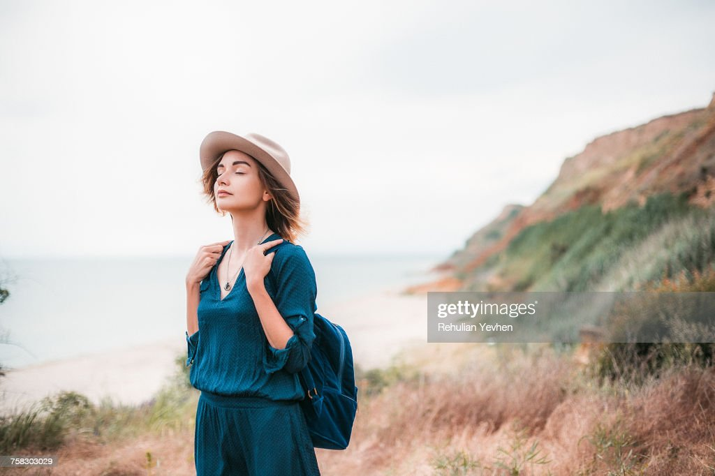 Mid adult woman in coastal setting, carrying backpack, breathing in fresh air : Stock Photo