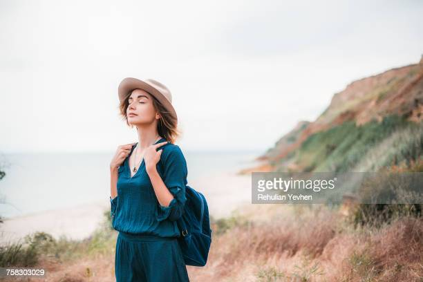 mid adult woman in coastal setting, carrying backpack, breathing in fresh air - non urban scene stock pictures, royalty-free photos & images