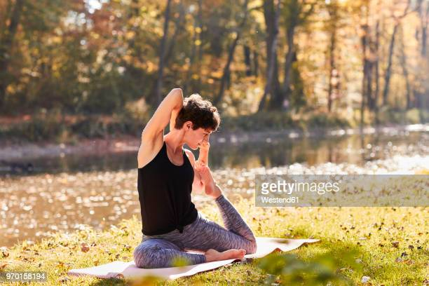 mid adult woman in forest practicing yoga - yogi stock photos and pictures
