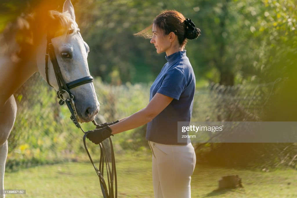 Mid adult woman in front of her white horse : Stock Photo