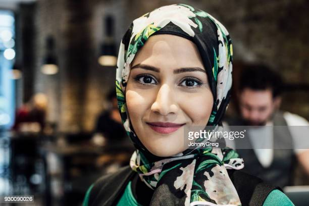 Mid adult woman in hijab smiling towards camera close up