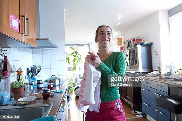 Mid adult woman in kitchen drying hands on tea towel looking away smiling