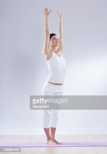mid adult woman in mountain pose against white background