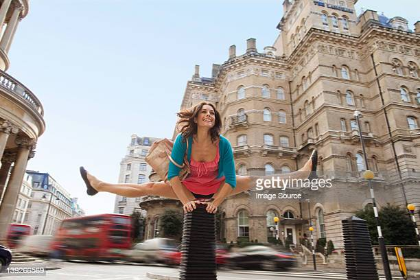 mid adult woman in pink dress leapfrogging through city street - legs spread woman stock photos and pictures