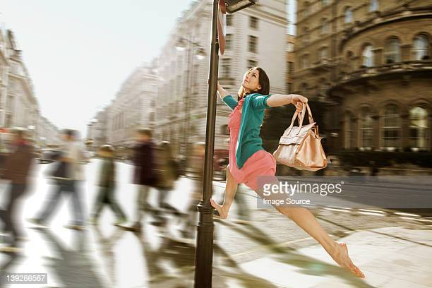 Mid adult woman in pink dress leaping through city streets