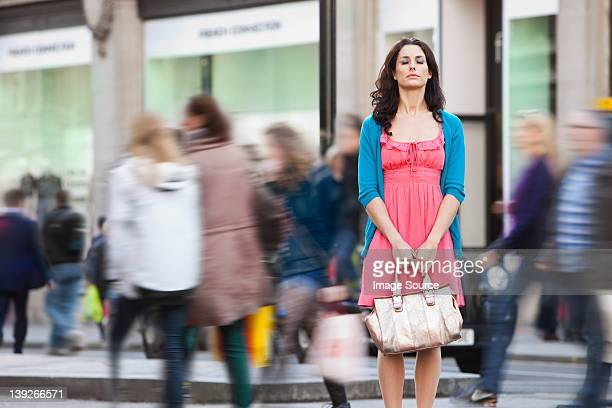 mid adult woman in pink dress standing still in crowded city - stationary stock pictures, royalty-free photos & images