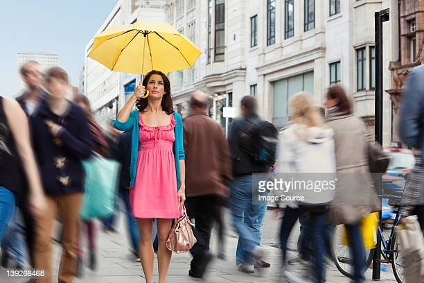 Mid adult woman in pink dress standing still with umbrella in crowded city