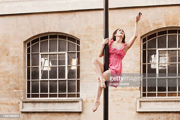 mid adult woman in pink dress using cellphone on street lamp in city - extra long stock pictures, royalty-free photos & images