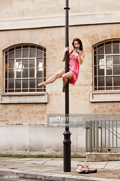Mid adult woman in pink dress using cellphone on street lamp in city