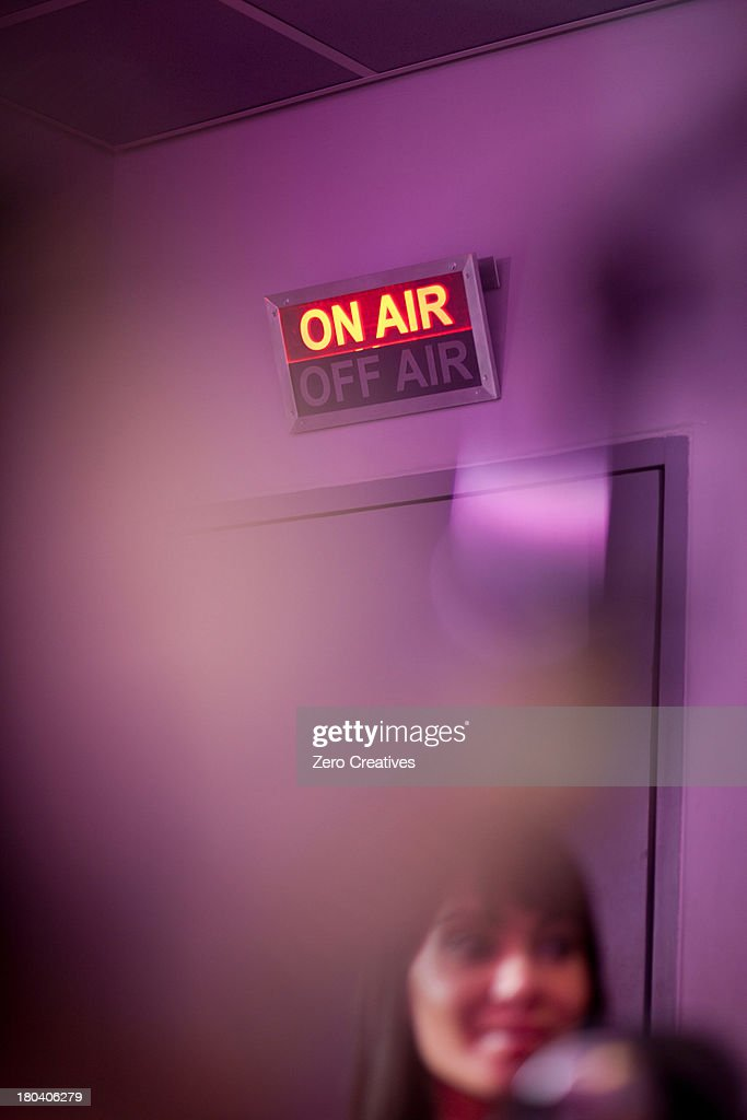Mid adult woman in recording studio with illuminated sign : Stock Photo