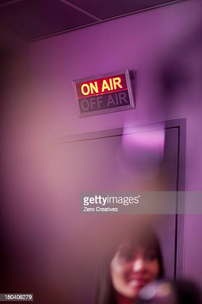Mid adult woman in recording studio with illuminated sign