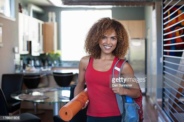 Mid adult woman in red vest and holding yoga mat, portrait