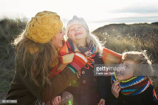 Mid adult woman in sand dunes with son and daughter wrapped in blanket