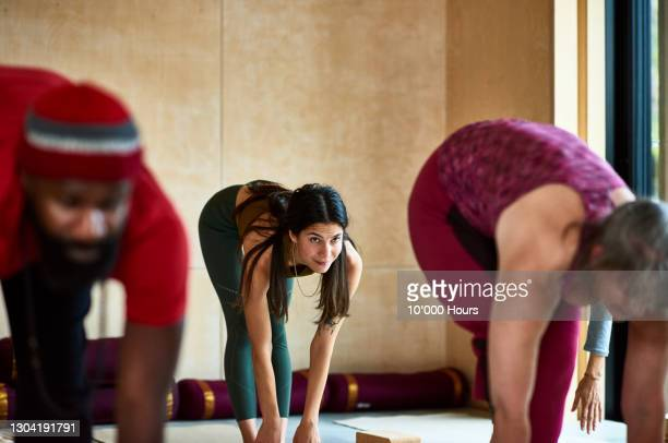 mid adult woman in standing forward bend in yoga class - part of a series stock pictures, royalty-free photos & images