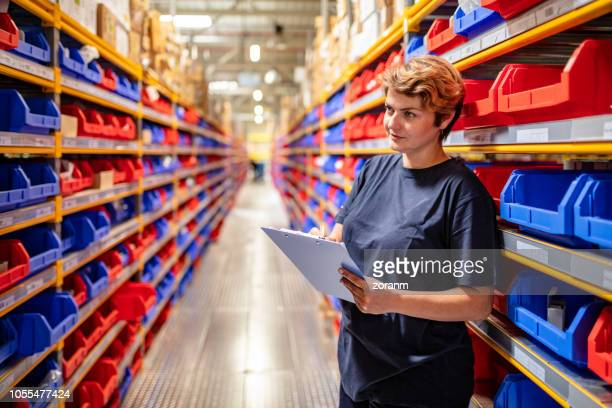 mid adult woman in warehouse with clipboard - industrial storage bins stock pictures, royalty-free photos & images