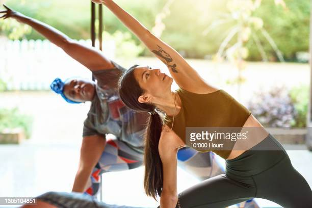 mid adult woman in yoga position with arm raised looking up - limb body part stock pictures, royalty-free photos & images
