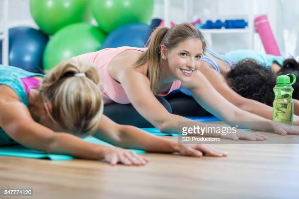 Mid adult woman is distracted during yoga class stretches