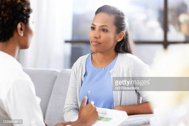 mid adult woman is upset and uncomfortable with therapist's questions - women's issues stock pictures, royalty-free photos & images