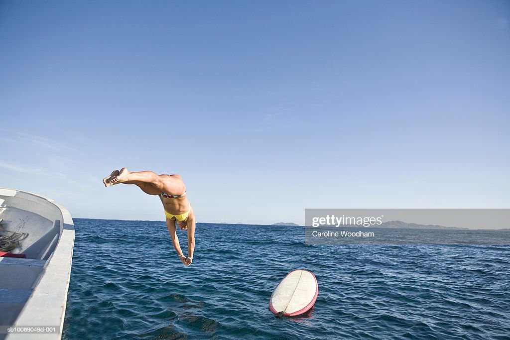 Mid adult woman jumping from boat into sea : Stockfoto