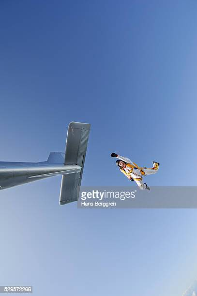 Mid adult woman jumping out of airplane
