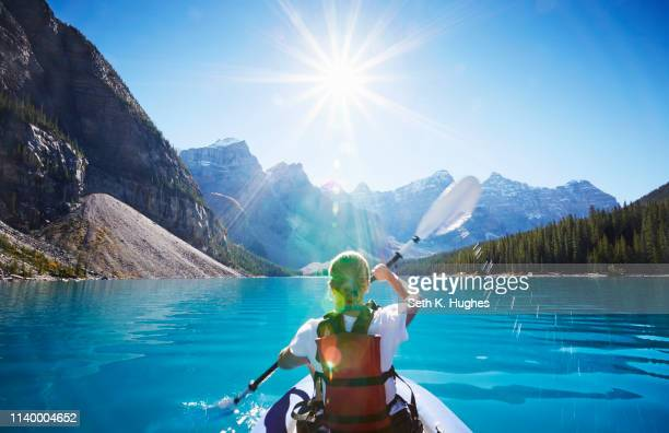 mid adult woman kayaking, moraine lake, alberta, canada - banff national park stock pictures, royalty-free photos & images