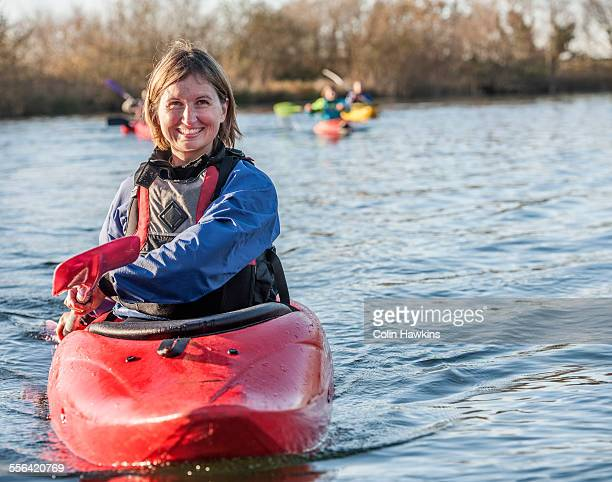 Mid adult woman kayaking on lake, portrait