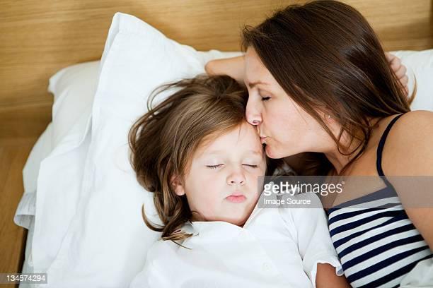 Mid adult woman kissing sleeping daughter