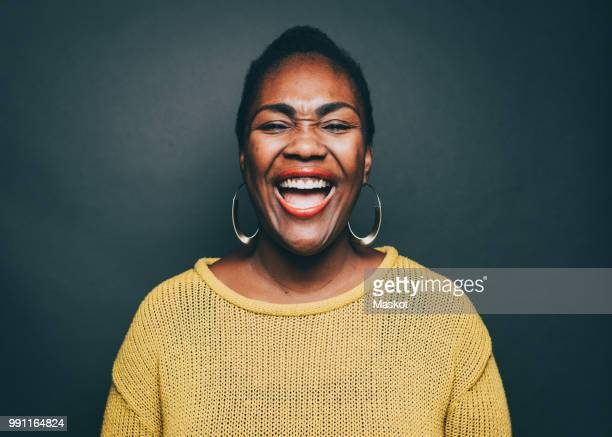 mid adult woman laughing over gray background - mouth open stock pictures, royalty-free photos & images