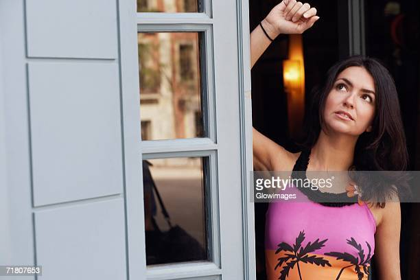 Mid adult woman leaning against a door and looking up