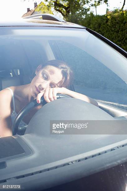 Mid adult woman leaning against steering wheel unconscious