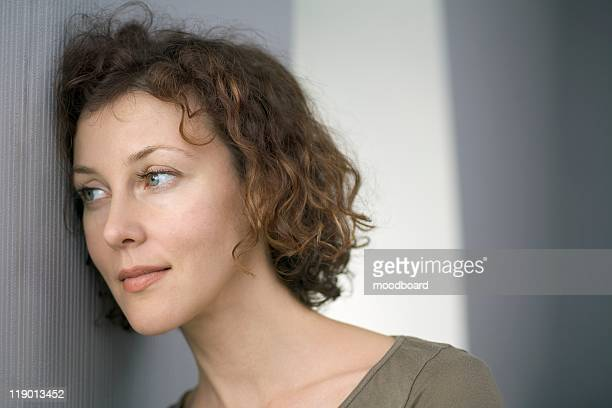 Mid adult woman leans against wall