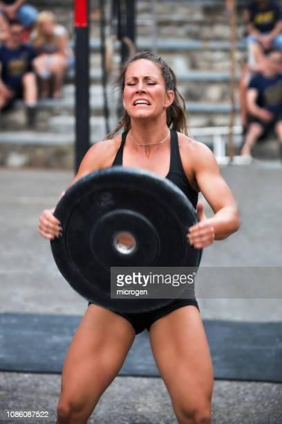 mid adult woman lifting weights while standing outdoors - levantamento de peso imagens e fotografias de stock
