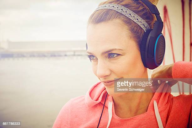 Mid adult woman listening to headphone music on rooftop parking lot