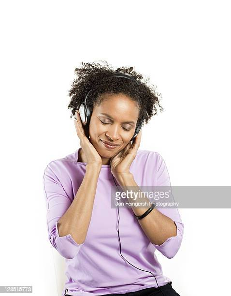 Mid adult woman listening to music with headphones