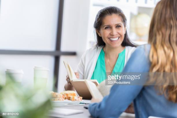 mid adult woman listens during book discussion at lunch - book club meeting stock pictures, royalty-free photos & images
