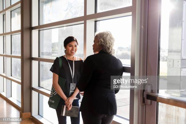 mid adult woman listens eagerly to mature conference speaker - town hall meeting stock pictures, royalty-free photos & images