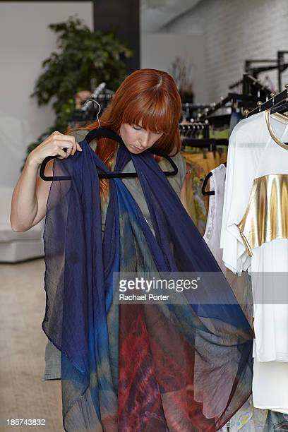 Mid adult woman looking at dress in clothes shop