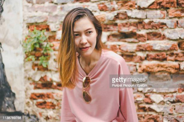 mid adult woman looking away while sitting against brick wall - thai mueang photos et images de collection