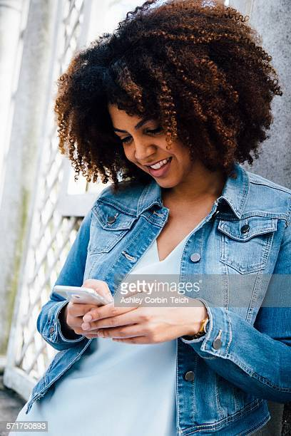 Mid adult woman looking down at smartphone smiling